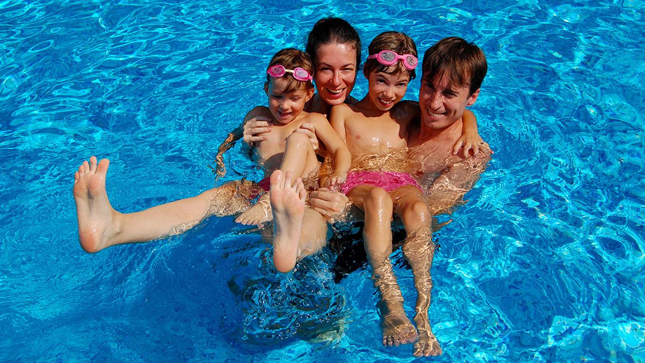 Perhe (isä, äiti ja kaksi lasta) uima-altaassa.