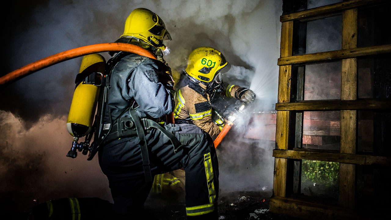 Kaksi palomiestä sammuttaa tulipaloa.